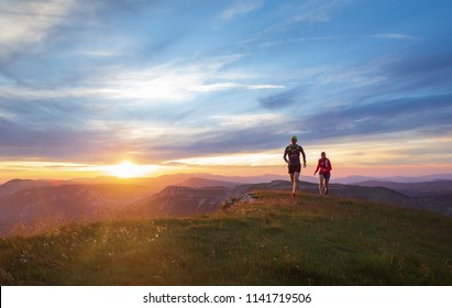 Two athletes trail running in the hills during a beautiful sunset. Shallow D.O.F.