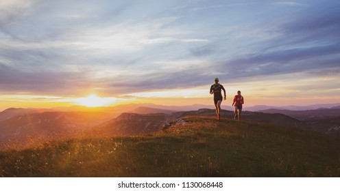 Two athletes trailrunning in the mountains during a nice sunset. Shallow D.O.F. and old film effect.