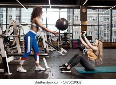 Two athletic girls dressed in a sportswear  are doing exercises for the press on the mat for fitness with fitness ball in the gym