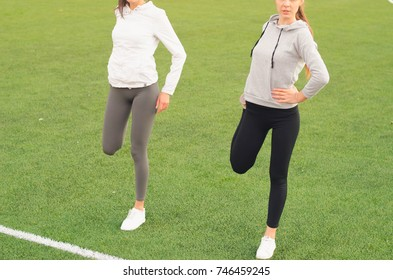 Two athletic girls stretching body before doing exercises. Sport and training. Sport tight clothes. Sporty girls. Fitness concepts. Outdoor