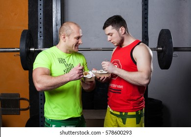 Two athletic men are eating after fitness training at the gym