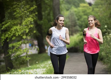 Two athletic woman running outdoors. Action and healthy lifestyle concept.