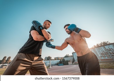 Two athletic young men boxing . Men training outdoors . Training kickboxing.Two males boxing outdoors. Sparring training box outside sport concept.
