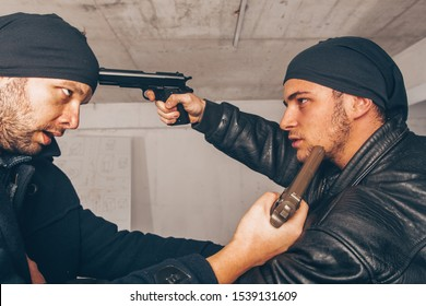 Two attackers are fighting and pointing a gun on one another's head