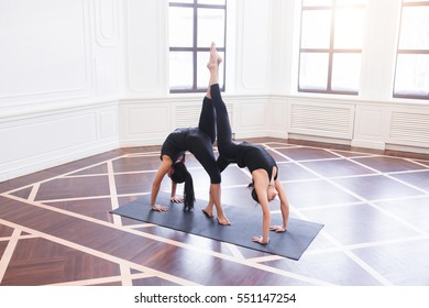 Two attractive asian sport girls work out yoga asana downward facing dog, Adho Mukha Svanasana, on black mat in fitness class. Group of young women stretching in gym with windows