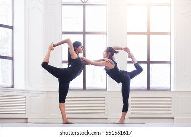 Two attractive asian sport girls work out yoga asana lord of the dance pose, Natarajasana, on black mat in fitness class. Group of young women stretching in gym with windows