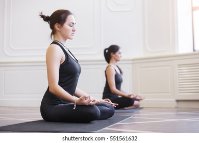 Two attractive asian sport girls work out yoga on black mat in fitness class. Group of young women stretching in gym with windows