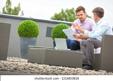 Two attractive business man sitting outdoors and discussing work whilst looking at laptop, they are casually dressed and culd be in a new start up business