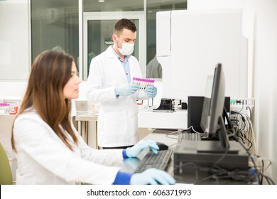 Two attractive chemists analyzing some blood and creating a report in a clinical laboratory