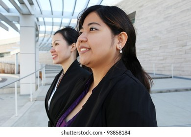 Two attractive Chinese business women at office building