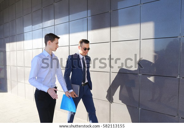Two attractive confident young businessman male guys go and discuss important issues, hurry to a meeting, make decisions, solve problems, share business ideas, smiling, holding colored folders in
