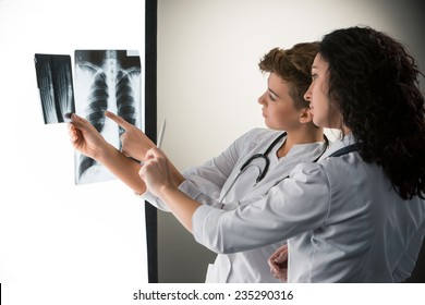 Two  attractive doctors looking at x-ray results on a gray background