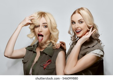 Two attractive fashion models, happy and joyful. Natural makeup, red lips and blue eyes.