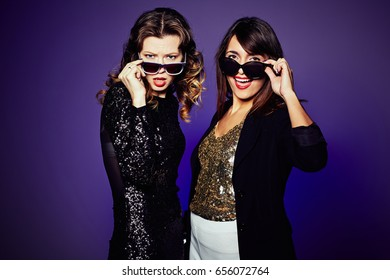 Two attractive fashion models posing for photography with stylish sunglasses while standing against dark background, studio shot