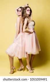 Two attractive and funny girlfriends wearing in pink dresses, sunglasses like princes having fun and making face. Women dancing, posing, holdig skirt in hand. Shopping concept.