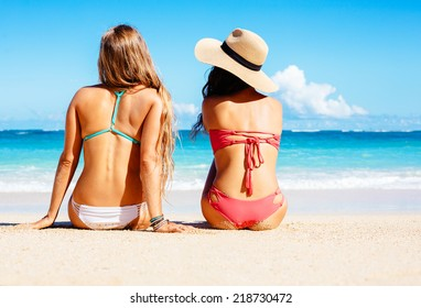 Two Attractive Girls in Bikinis Sitting on Sunny Tropical Beach