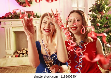 Two attractive girls celebrating New year. Young woman in blue dress with young woman in red dress holding wineglasses with champagne