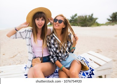 Two attractive girls, cheerful best friends having fun at beach party. Wearing summer outfit, shorts and t-shirts,having fun fashionable looking with beautiful wavy hair. Isolated.hat and sunglasses