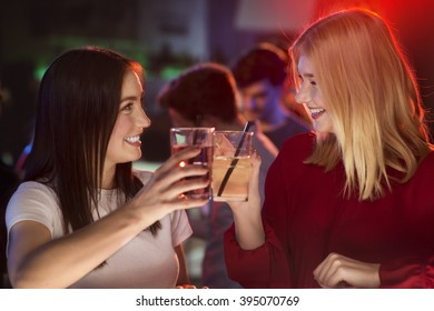 Two attractive girls clink their glasses at bar and smiling