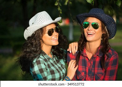 Two attractive girls in cowboy hats and sunglasses walking park. happily  laughing fd1c7d956901