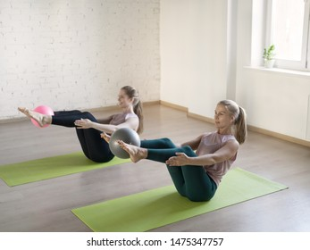 Two attractive girls doing boat pose with small fit balls in fitness studio, selective focus. Training abs and balance. Yoga, workout, pilates, exercise therapy, flexibility, sport, wellness, activity