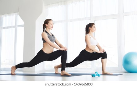 Two attractive girls doing stretching exercises on white background in yoga class, copy space, studio, healthy life concept