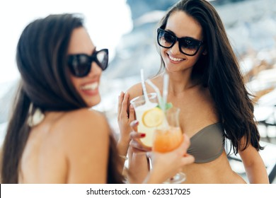 Two attractive girls drinking cocktails on beach