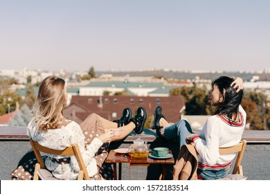 Two attractive girls enjoy a tea party on the rooftop overlooking the city. Drinking healthy buckwheat tea. Healthcare or herbal medicine concept.
