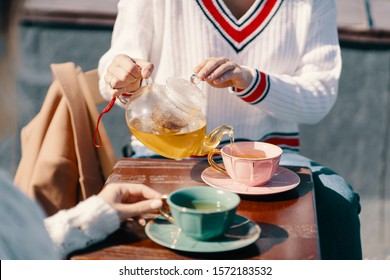 Two attractive girls enjoy a tea party. Drinking healthy buckwheat tea. Healthcare or herbal medicine concept. Close-up on mugs