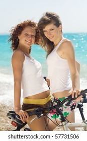 Two attractive girls on a beach with bicycles
