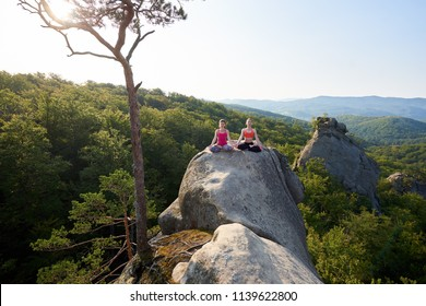 Two attractive girls sit meditating in lotus pose, lit by summer sun, on the top of huge rock on mountain forest and clear blue sky background. Yoga, fitness and healthy lifestyle concept. Siddhasana