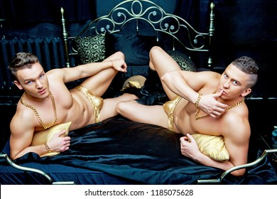 two attractive muscular men wearing  golden chains and underwear   in bed with black linen