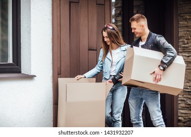 Two attractive people in casual wear moving to new house with cardboxes.