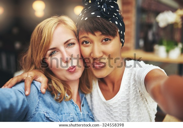 Two attractive playful young women standing arm in arm blowing a kiss at the camera puckering up their lips with a teasing smile
