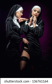 Two attractive sexy nuns posing indoors