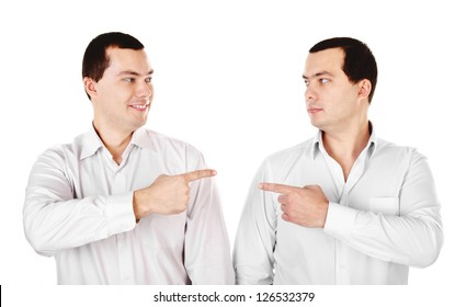 Two attractive smiling young men twins showing at each other isolated on white