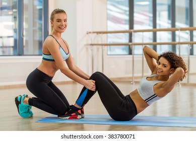 Two attractive sport girls smiling while working out and doing abs in fitness class