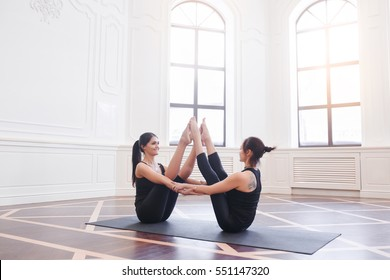 Two attractive sport girls work out nauka asana boat yoga pose on black mat in fitness class. Group of young women stretching in gym with windows