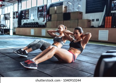 Two attractive sporty women are working out in gym. Cross fit. Abs training.
