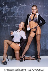 two attractive striptease dancers dressed as teachers against a chalkboard in the classroom