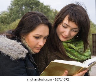 Two attractive students reading book in city park