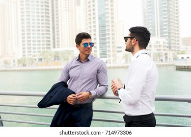 Two attractive stylish businessmen leaned on the fence having a conversation.