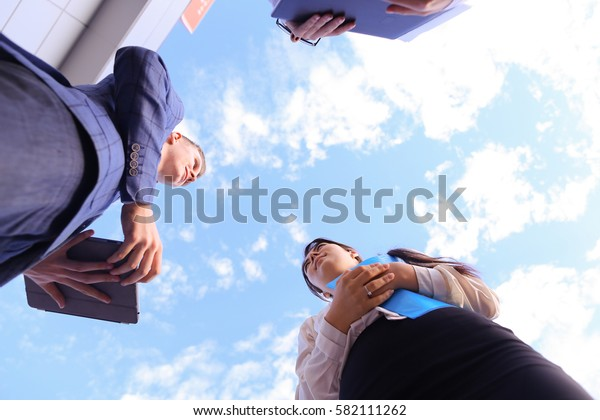 Two attractive successful woman and beautiful modern man, successful young office workers, businessmen, students communicate, make deal, shake hands, discuss working moments, versed in reports, kept
