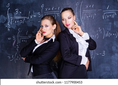 two attractive teachers against a chalkboard in the classroom
