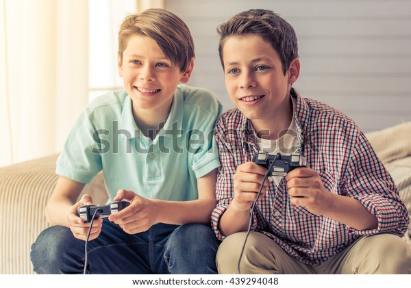 Two attractive teenage boys are playing game console and smiling while sitting on the couch at home
