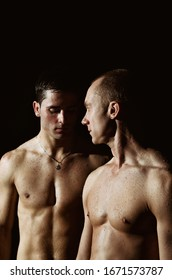 Two attractive wet guys. Black background.