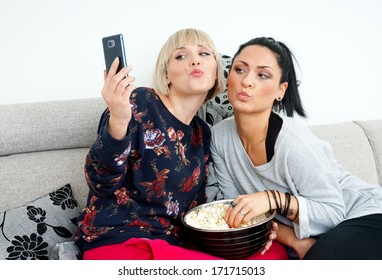 two attractive woman friends using mobile phone to make selfi picture on the sofa