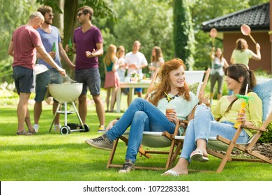 Two attractive women chatting at a garden party with many friends grilling, playing badminton, and eating