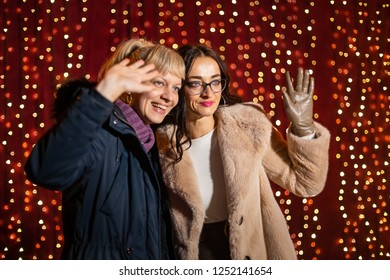 Two attractive women posing for photo in front of light wall at Christmas market.