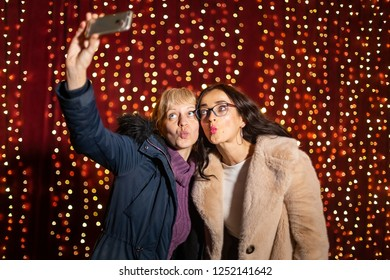 Two attractive women taking selfie in front of light wall at Christmas market.